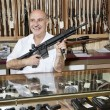Happy mature man with rifle in gun store — Stock Photo