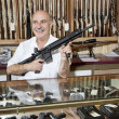 Happy mature man with rifle in gun store — Stock Photo #21879767