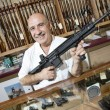 Stock Photo: Portrait of a happy mature merchant with rifle in gun shop