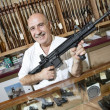 Portrait of a happy mature merchant with rifle in gun shop - Stock Photo