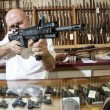Mature merchant aiming with rifle in gun shop - Stock Photo