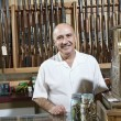 Portrait of a mature merchant in gun shop — Stock Photo