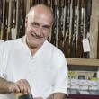 Portrait of a mature merchant with credit card reader in gun shop - Stock Photo
