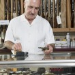 Mature male merchant at gun shop with credit card reader — Stock Photo