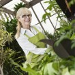 Stock Photo: Portrait of happy senior gardener cultivating plants in greenhouse