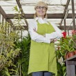 Portrait of a happy female gardener standing with arms crossed in botanical garden — Stock Photo
