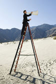 Businessman On Stepladder Using Megaphone In Desert — Stock Photo