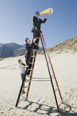 Business on Stepladder Using Megaphone in Desert — Stock Photo