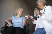 Doctor Giving Medicines To Disabled Patient — Stock Photo
