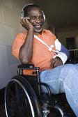 Injured Man Listening Music While Sitting On Wheelchair — Stock Photo