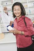 Kobieta podnoszenia leków na receptę w aptece — Zdjęcie stockowe