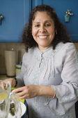Femme d'âge mûr souriante cuisine dans cuisine — Photo