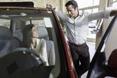 Couple talking in car show room — Stock Photo
