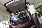 Padre a hijo sentado en el baúl del auto en el showroom — Foto de Stock
