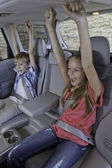 Cheerful children sitting at the back seat of car — Stockfoto