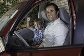 Allegro ragazzo seduto in macchina con suo padre — Foto Stock