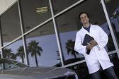 Concessionario auto felice in piedi davanti all'autosalone — Foto Stock