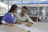 Man och kvinna underteckna papper — Stockfoto