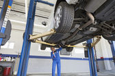 Low angle view of mechanic working under car — Stock Photo