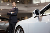 Confident car salesperson standing with arms crossed — Stock Photo