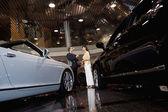 Salesman talking to woman in automobile showroom — Stock Photo