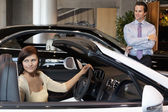 Woman having a test drive while salesperson standing besides car — Stock Photo