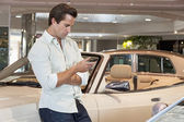 Man standing besides car with his mobile phone — Stock Photo