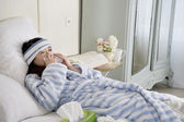 Young woman lying on bed with common cold — Stock Photo