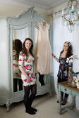Sisters holding dress hanged on hanger — Stock Photo