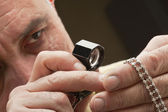 Close up of man looking at jewelry through magnifying glass — Stock Photo