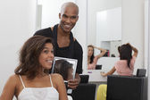 Hairdresser holding a mirror behind young woman — Stock Photo