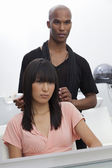 Asian woman sitting on chair with hairstylist standing behind — Stock Photo
