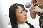 Hairstylist giving a haircut to Asian woman — Stock Photo