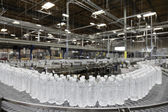 Bottled water on conveyor at bottling plant — ストック写真