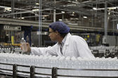 Factory worker examining bottled water — Stock Photo
