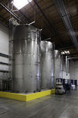 Huge silos and a forklift at bottling plant — Stock Photo