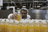 Quality control worker checking juice bottle on production line — Stok fotoğraf