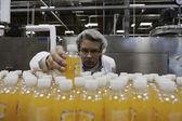 Trabajador de control de calidad control botella de jugo en la línea de producción — Foto de Stock