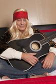 Sorrindo sênior guitarrista sentado com pernas cruzadas — Fotografia Stock