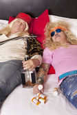 Two drunk male friends reclining on bed — Stock Photo
