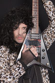Portrait of middle-aged man wearing leopard skin pattern with electric guitar — Stock Photo
