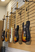 Five electric guitars hanging on display rack in store for sale — Stock Photo