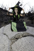 Little young girl costumed as witch sitting on rock looking away — Stock Photo