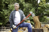 Senior lumber jack holding an axe and looking away — Stock Photo
