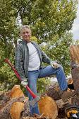 Lenhador com um pé de machado com a pilha de lenha picada no fundo — Fotografia Stock