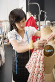Female fashion designer pinning costume on mannequin — Stock Photo