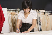 Young fashion designer working at her clothing store — Stock Photo