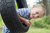 Portrait of a young boy winking while swinging on tire — Stock Photo
