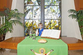 Little boy standing by the altar table — Stock Photo