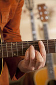 Close-up of mid adult man's fingers while playing guitar — Stock Photo